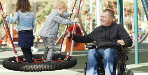 Man in a wheelchair pusjing children on swings at a playground.