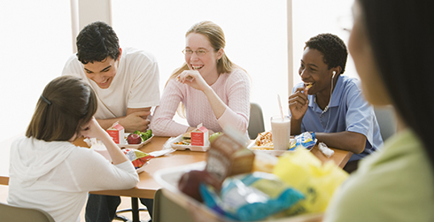 Four teenagers laughing at a lunch table while another girl looks on.