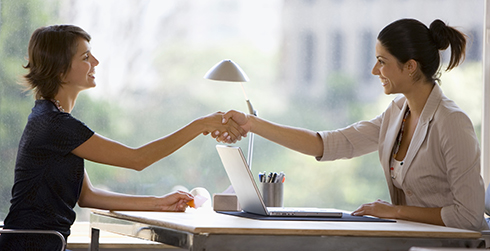 Employer and employee shaking hands across a desk.