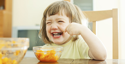 A little girl laughing and eating fruit.