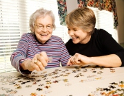 An older woman and a young woman working on a puzzle.